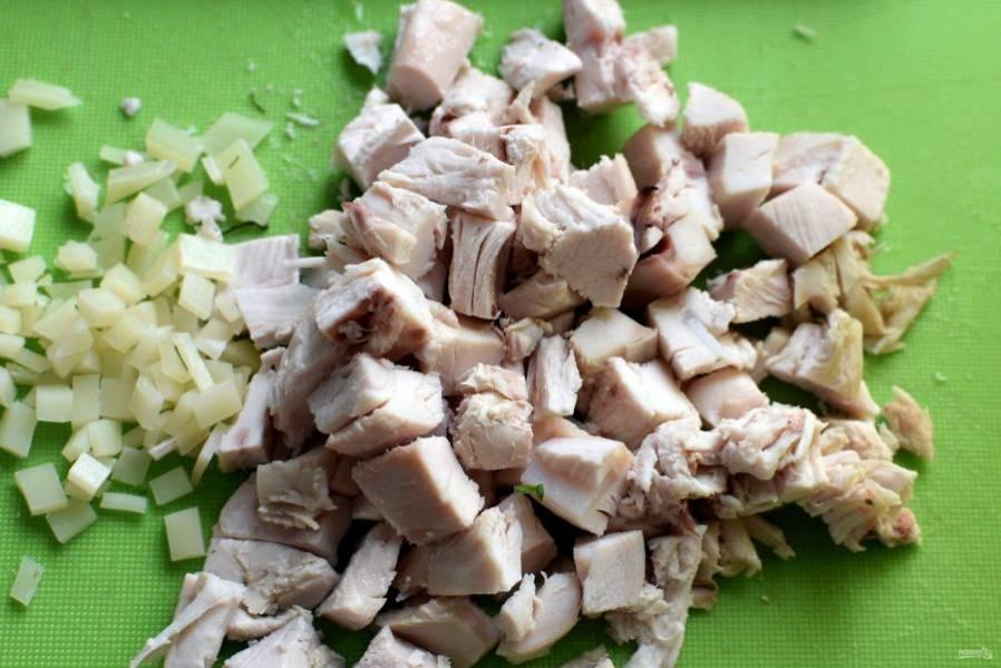 Включите духовку на разогрев до 200 градусов и начните готовить начинку. Нарежьте кубиками отварную грудку, сыр натрите на крупной терке или мелко нарежьте.