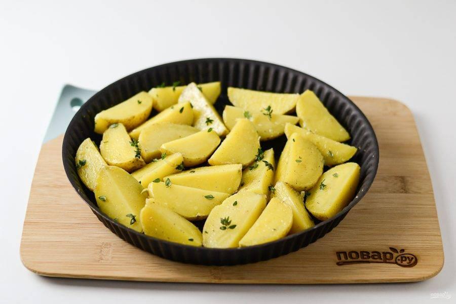 Выложите картофель на противень в один слой. Запекайте в разогретой до 200 градусов духовке 25 минут.
