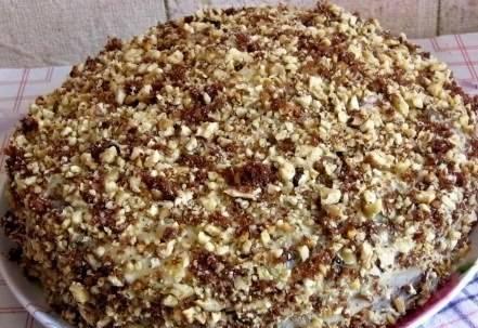 4. Смазываем наши коржи кремом и посыпаем орехами со всех сторон. Я беру обычно грецкие орехи, ставлю их на 10 минут в духовку, после чего разминаю скалкой и посыпаю ими торт.