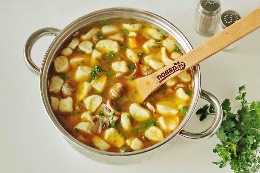 В кипящую воду опустите картофель, дождитесь закипания и добавьте галушки. Добавьте по вкусу специи, соль и варите 10-15 минут до полной готовности всех ингредиентов. За 5 минут до окончания варки, добавьте обжаренные овощи с грибами. Когда грибной суп с галушками будет готов, добавьте измельченную свежую зелень. Дайте супу настояться 15-20 минут и подавайте к столу.