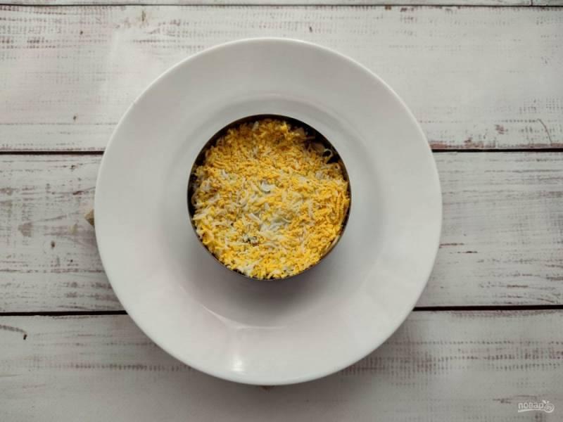Яйца очистите от скорлупы, натрите на мелкой терке, выложите поверх грибов и смажьте майонезом.