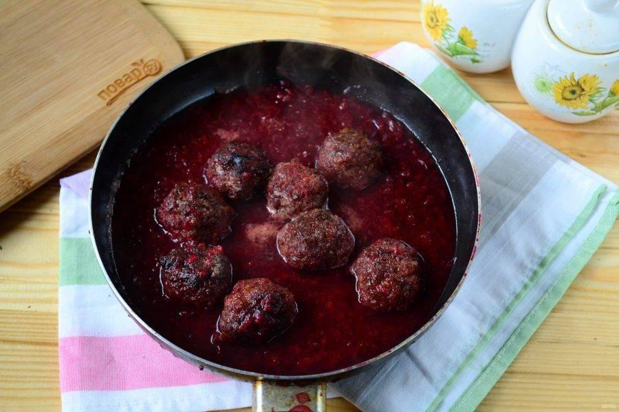 Верните вишневый соус в сковороду, выложите в него фрикадельки, перемешайте, чтобы все фрикадельки были покрыты соусом, и тушите на медленном огне 10-12 минут.