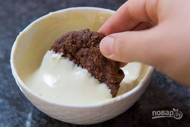 Половинку остывшего печенья окуните в растопленный белый шоколад.
