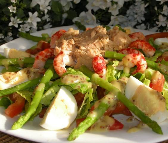 """Отварить спаржу, салат порвать руками, разложить на большой тарелке листья салата с полосками помидора, сверху одним куском тунец, вокруг раковые шейки, дольки яйца, заправить соусом. Салат """"Чикаго"""" готов."""
