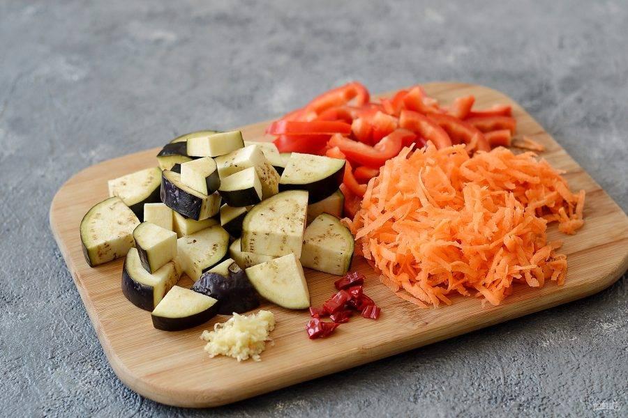 Морковь натрите на крупной терке, болгарский перец нарежьте соломкой. Баклажаны нарежьте крупными ломтиками. Чеснок пропустите через пресс.