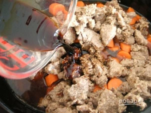 Сверху положите мясо, всыпьте перец и травы, влейте бульон и вино.
