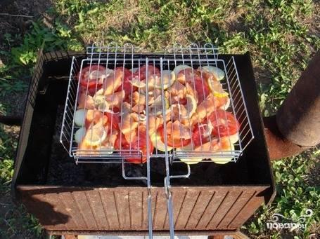 Уложите на решетку рыбу, лук и помидоры, порезанные кольцами. Жарьте на углях до готовности примерно 10-12 минут.