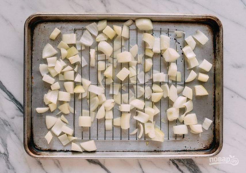 1.Очистите лук и нарежьте его крупно. Возьмите форму для запекания с сеткой, половину лука уложите под сетку, вторую - на.