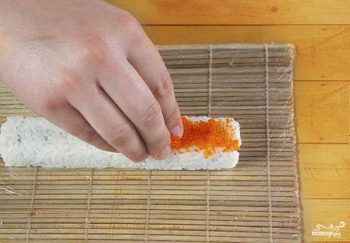 6. Выложить на ролл икру летучей рыбы. Закатать циновку, чтобы икра равномерно распределилась по поверхности.