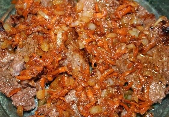Далее пассируем на масле нарезанный лук и тертую морковь, выкладываем обжаренные овощи на мясо.