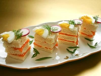 1. Малосоленый или копченый лосось может стать отличным ингредиентом для канапе. Ломтик белого хлеба необходимо нарезать на небольшие кусочки. Смазать сливочным маслом и выложить тонко нарезанный лосось. Повторить слои 2-3 раза и нанизать на шпажку. Дополнить такие канапе можно кусочком яйца, ломтиком огурчика или свежей зеленью. Такие небольшие бутербродики будут отлично смотреться на праздничном столе.