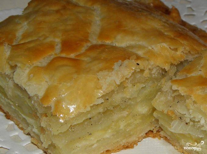 Пирог выложите на противень. Так как слоеное тесто само по себе достаточно жирное, дополнительно смазывать его маслом не нужно. Духовку разогрейте до ста семидесяти градусов, запекайте пирог на протяжении часа.