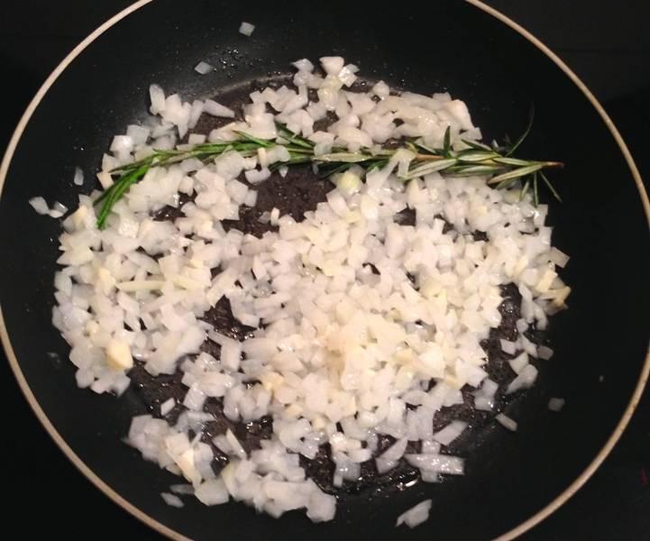Нагреваем в сковороде небольшое количество оливкового масла и обжариваем на нем мелко нарезанный репчатый лук и чеснок, добавляем веточку розмарина.