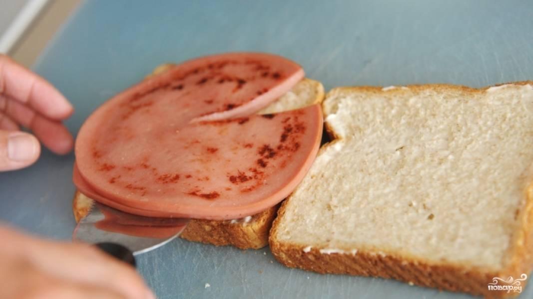 Смажьте оба ломтика хлеба сливочным сыром. Уложите на один ломтик варёную колбасу.