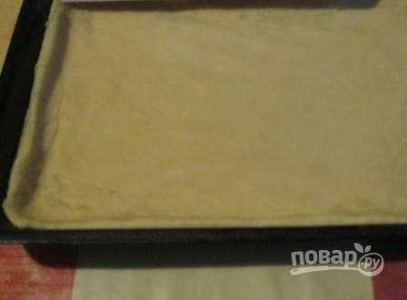 Раскатываем тесто в пласт толщиной примерно 7-8 мм. Слегка смазываем форму маслом и выкладываем пласт теста, формируя бортики.