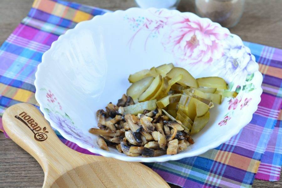 Огурцы переложите в миску. Добавьте обжаренные полосками грибы.