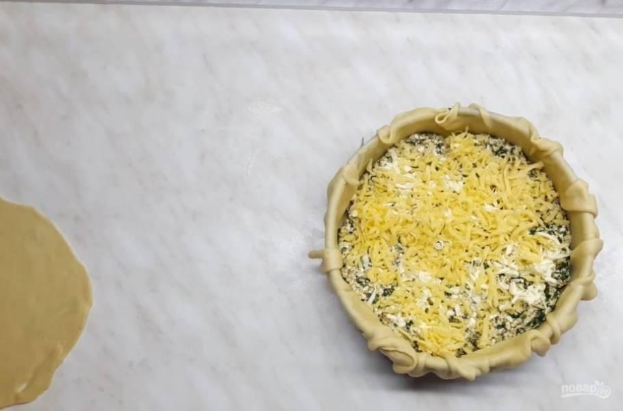 6. На основу выложите тертый твердый сыр, прикройте его небольшим кругом теста, выложите на него начинку, натрите ледяное сливочное масло, добавьте тертый сыр, накройте вторым кусочком теста и защипните края.