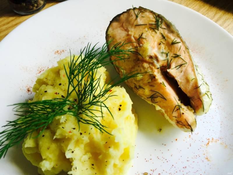 Готовую рыбу аккуратно достаньте лопаткой из мультиварки, чтобы не повредить её. На блюдо выложите картофельное пюре, рыбу, украсьте всё зеленью.