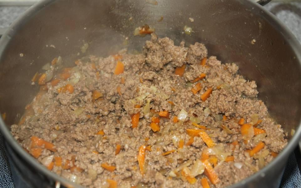 Добавьте говяжий фарш. Помешивая, жарим пока, он не поменяет цвет. Сразу же вливаем вино. Готовим, пока оно не испарится. Кладем помидоры в собственном соку и томатную пасту, вливаем стакан воды, добавляем соль и перец. Варим на медленном огне 35 минут.