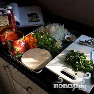 2. Между тем нагреть 3 столовые ложки оливкового масла в большой кастрюле. Добавить лук, сельдерей, морковь и жарить на медленном огне в течение 10 минут, пока лук не начнет коричневеть. Добавить чеснок и готовить еще 30 секунд. Добавить куриный бульон, помидоры с пюре, халапеньо, тмин, кориандр, 1 столовую ложку соли (в зависимости от солености куриного бульона), 1 чайную ложку черного перца и кинзу.