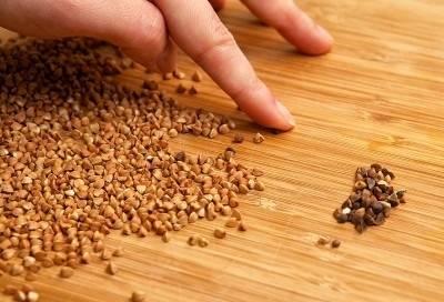Добавьте черный молотый перец, прикрутите плиту на маленький уровень, накройте сковороду крышкой и тушите подливу до полной готовности мяса в течение 1 часа. Периодически открывайте крышку и перемешивайте подливу кухонной лопаткой. Пока тушится мясо, начните готовить гречневую кашу. От общей массы крупы отделите нужное вам количество и высыпьте на чистый разделочный стол тонким слоем. Переберите гречку и удалите семена сорняков, оболочку, шелуху.