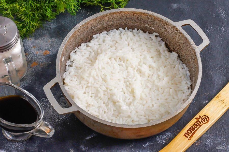Рис промойте в воде и всыпьте в казан или ковш, добавьте соль и залейте горячей водой. Отварите примерно 12-15 минут до полуготовности. Прогрейте уксус с сахарным песком до растворения и всыпьте в емкость к рису. Аккуратно перемешайте и остудите рис примерно 20 минут.