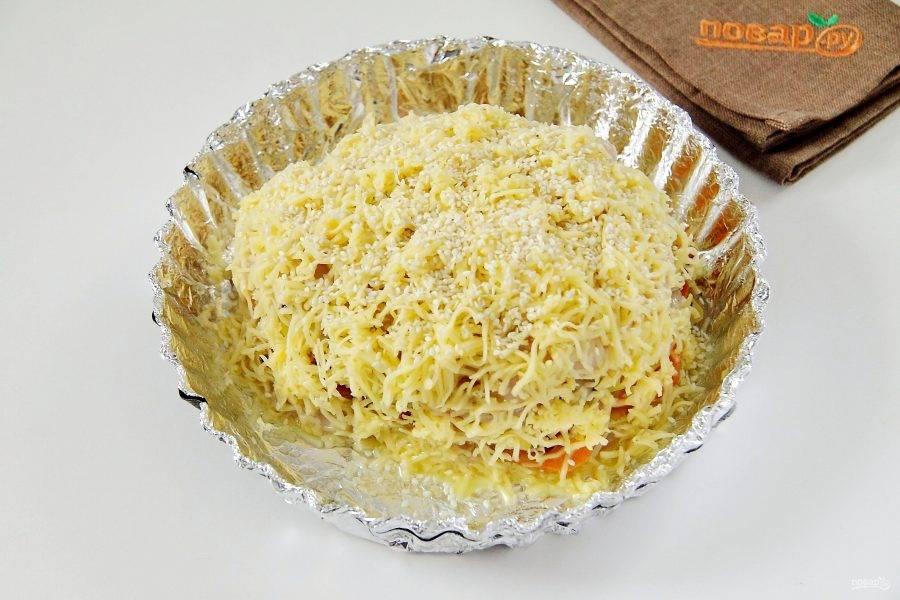 Смажьте мясо яйцом, посыпьте со всех сторон тертым сыром и кунжутом.