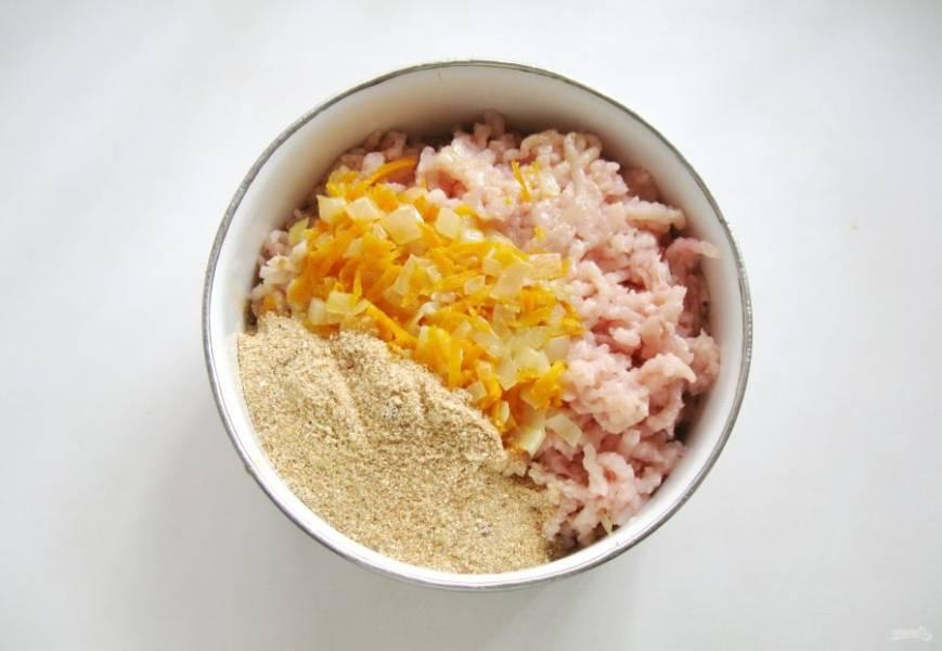Половину тушеных овощей(моркови с луком) выложите в миску с куриным фаршем. Добавьте панировочные сухари.