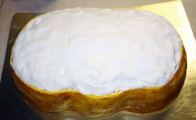 Верх торта украсьте взбитыми сливками со сгущенкой.
