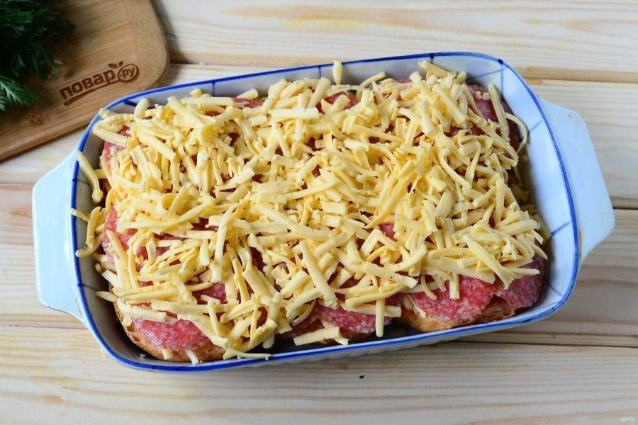 Сверху колбасу присыпьте второй половиной сыра.