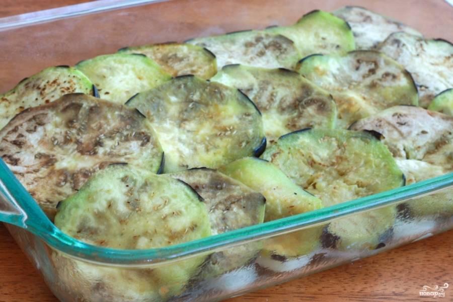 2. Дальше - слой баклажанов. Чтобы не горчили, я их картофелечисткой частично избавила от темной кожуры и обжарила со специями. Баклажаны выкладываем не все сразу, а только половину.