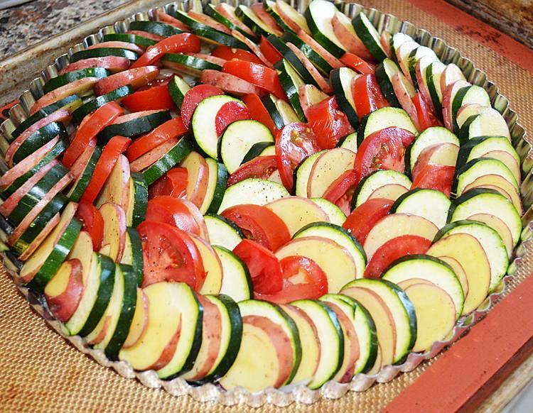 2. Теперь красиво выкладываем по кругу, чередуя разные овощи. Добавляем соль и специи по вкусу и посыпаем мелко натертым сыром.