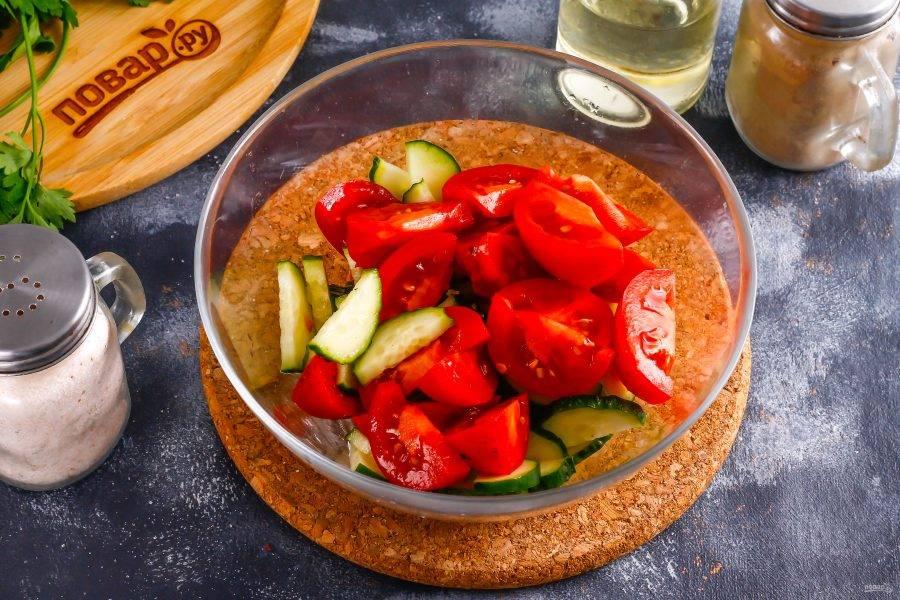 Промойте огурец и помидоры в воде, вырежьте из томатов зеленые сердцевинки, а с огурца срежьте хвостики. Нарежьте огурец полукольцами, а помидоры — крупными ломтиками в глубокую емкость.