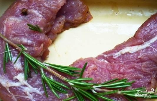 2. Протыкаем гвоздику в мякоть, сверху кладем веточку розмарина (можно ее обмотать вокруг мяса), посыпаем перцем и поливаем соком. Оставляем так мясо на 1 час.