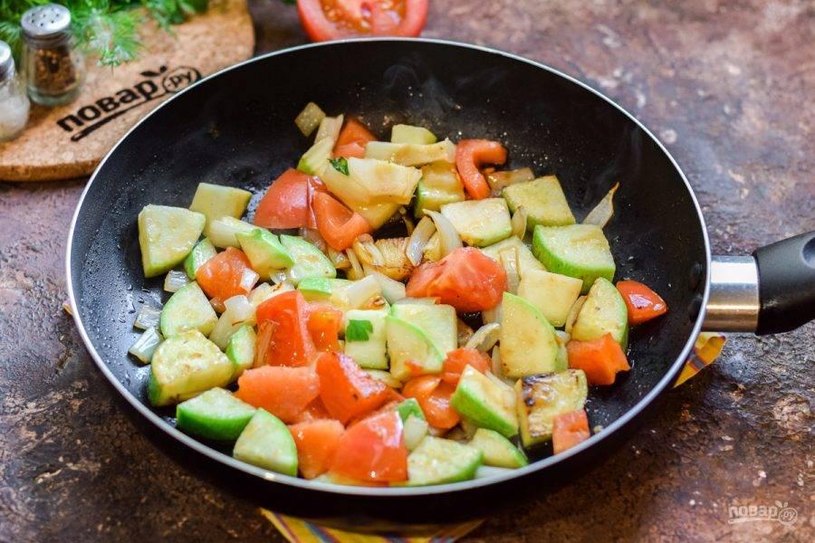 В сковороде прогрейте масло, выложите лук, кабачок и помидор, жарьте на среднем огне 10 минут.