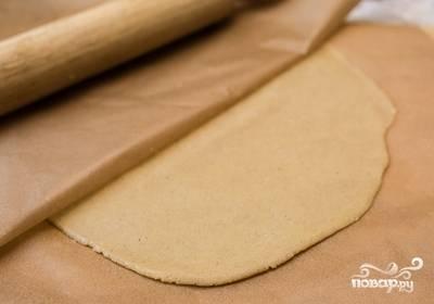 3.Каждую из частей положите между листами пергамента и раскатайте. Обрежьте корж по форме тарелки, примерно на 20 см. Выпекайте по 11 минут при температуре 180 С.