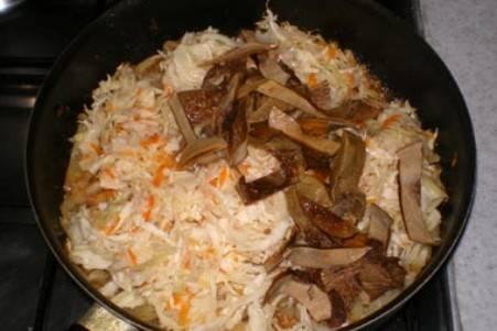 К капустно-луковой смеси добавьте квашеную капусту и грибы. Хорошенько перемешайте, продолжайте тушить  еще минут 15. Если вы увидите, что капуста стала прилипать к сковородке, добавьте еще немного воды и не забывайте помешивать.
