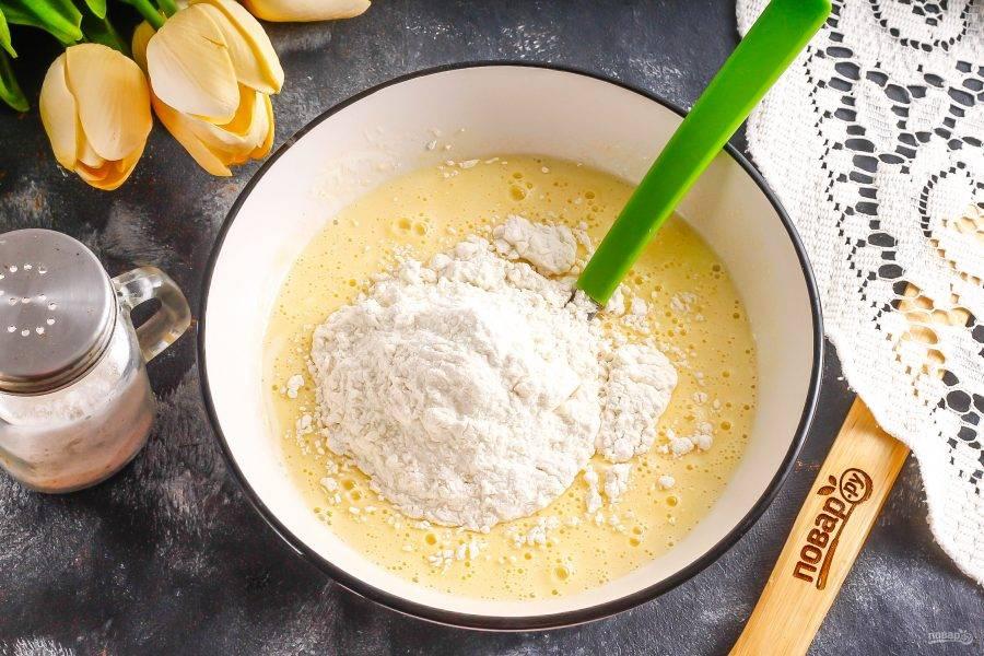 Добавьте по частям пшеничную муку, замешивая тесто.