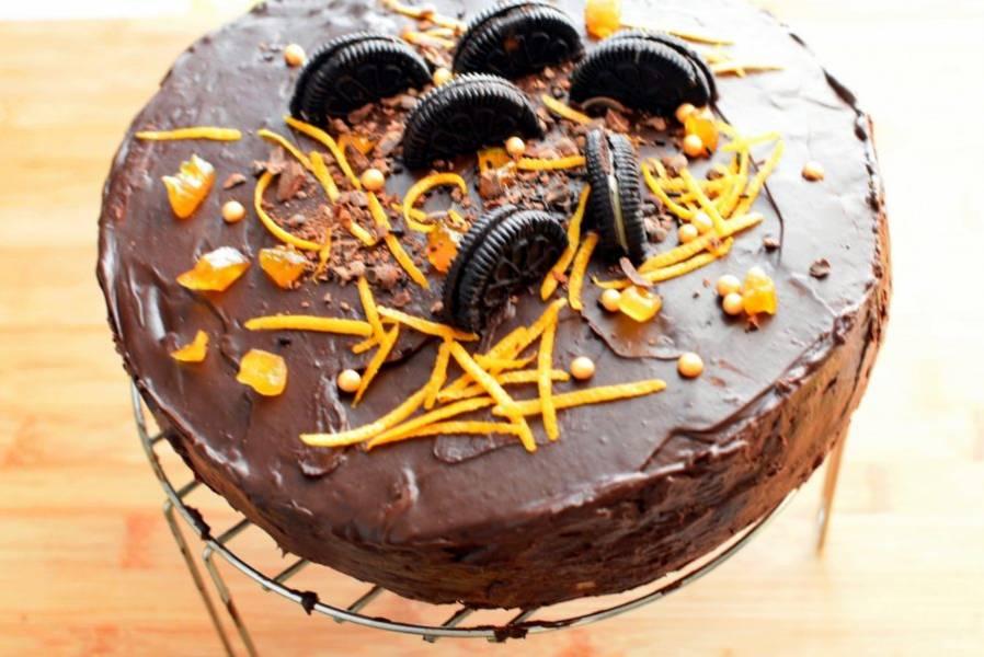 За это время приготовьте шоколадный ганаш. Нагрейте сливки, не доводя до кипения и залейте ими мелко рубленый шоколад. Хорошо перемешайте до расплавления шоколада. Немного остудите и полейте верх торта. Пока ганаш не застыл, украсьте торт по вашему умению и желанию.