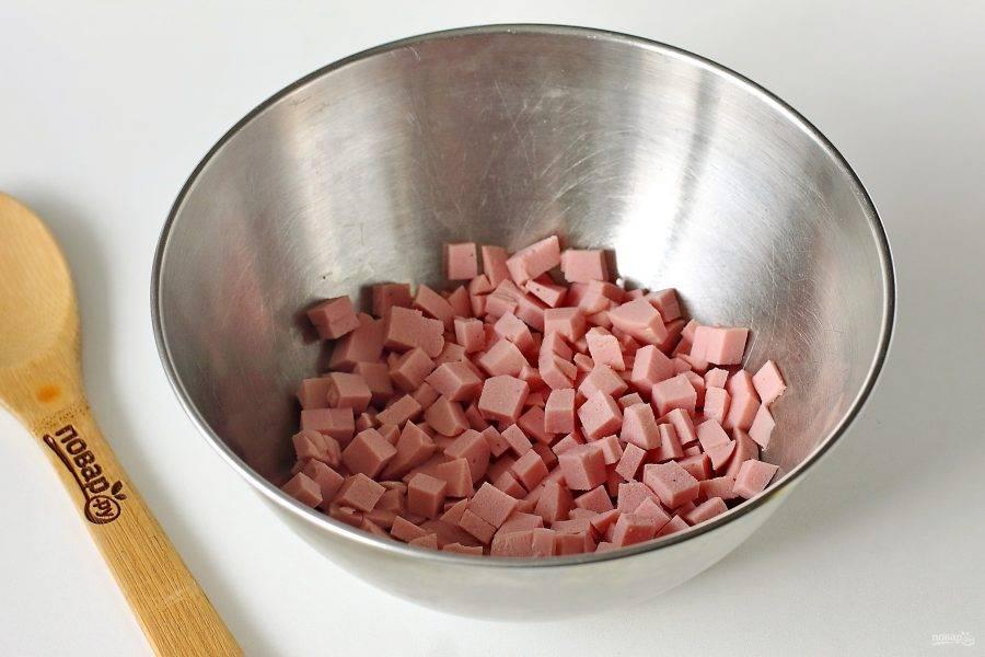 Колбасу нарежьте кубиками и сложите в глубокую миску.