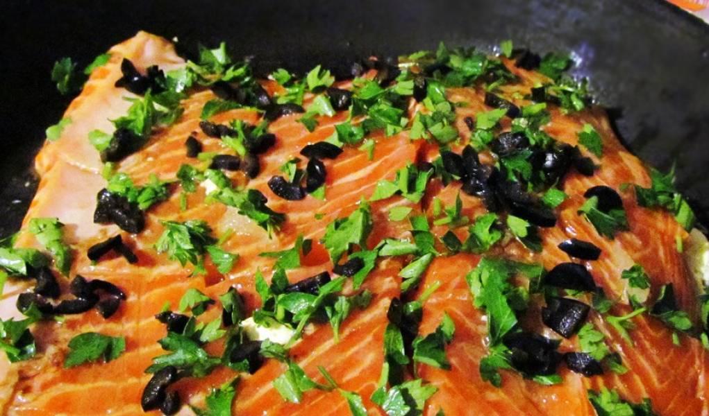 Смазываем сковороду сливочным маслом, выкладываем на неё филе семги. Присыпаем его специями, измельченными маслинами и петрушкой.