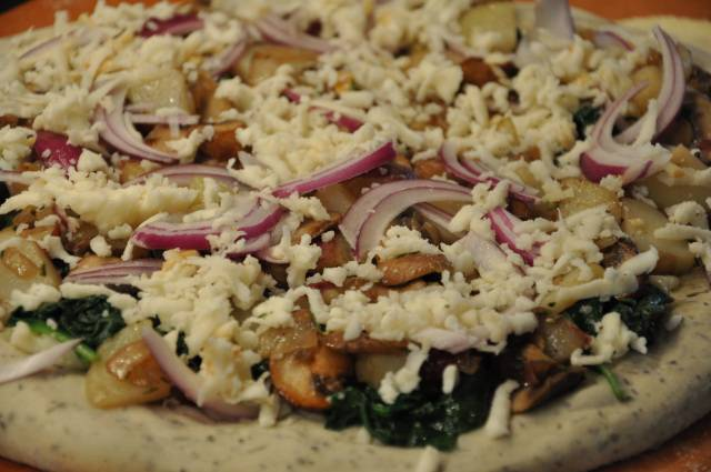 5. На тесто выложить обжаренный шпинат, а сверху - начинку. При желании можно добавить тонко нарезанный красный лук. Присыпать все тертым сыром и отправить в разогретую духовку. Пицца с картошкой и грибами в домашних условиях будет готова через 15-20 минут.