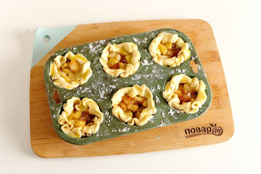 Наполните тесто яблочной начинкой и подверните края теста вовнутрь, чтобы получились корзиночки. Смажьте тесто желтком. Выпекайте в духовке при температуре 180-200 градусов около 20 минут.