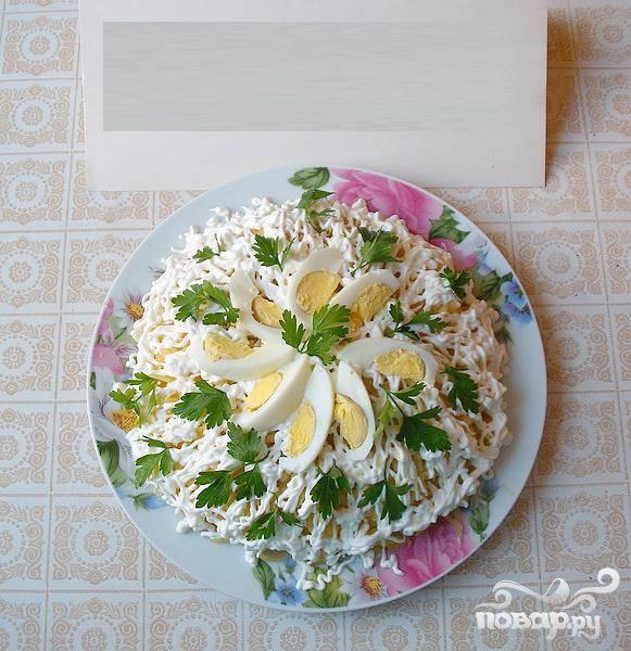 6.Сметанную тонкую сеточку наносим поверх картофеля (постараемся сделать это в форме цветочных лепестков). Веточками петрушки и ломтиками вареного яйца украшаем салат.