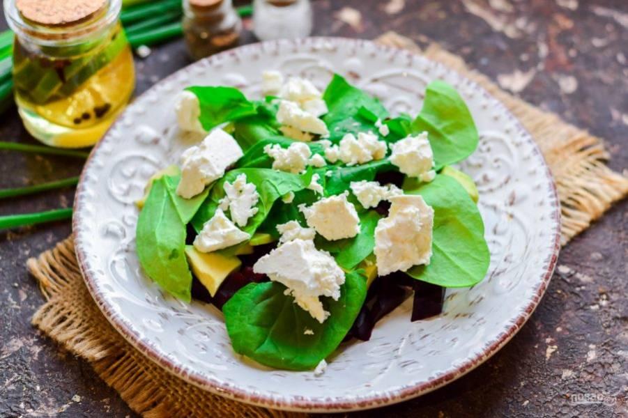 Шпинат сполосните и просушите, порвите руками и добавьте в салат. Брынзу также поломайте небольшими кусочками и добавьте в салат.