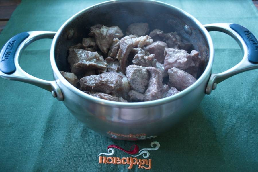 В толстостенную кастрюлю влейте растительное масло. Нарезанное мясо выложить в кастрюлю и обжарить со всех сторон. Мясо изменится в цвете.