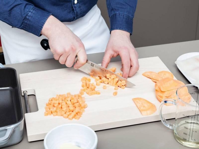 1. Батат помойте, почистите и нашинкуйте мелкими кубиками. Смажьте форму для выпечки небольшим количеством масла, потом выложите туда картофель.