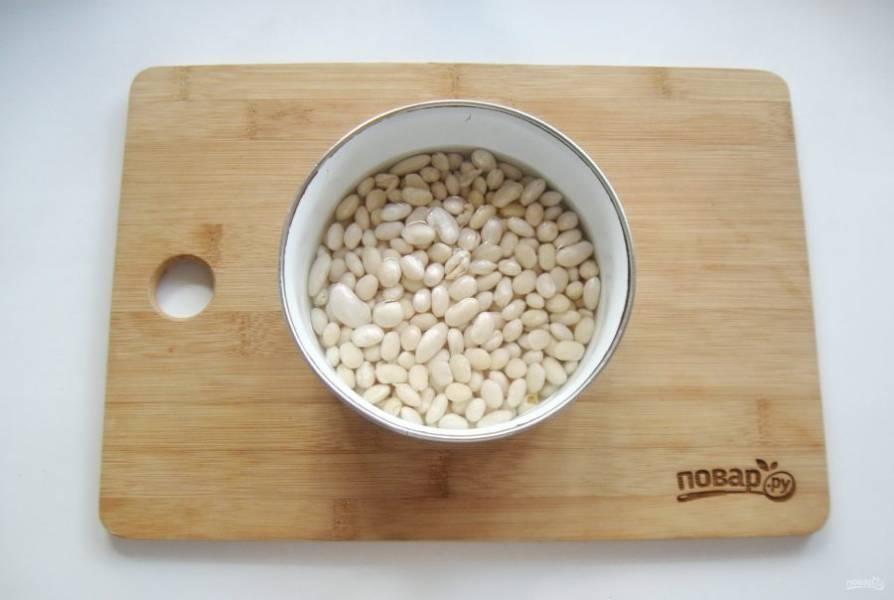Белую сухую фасоль помойте, выложите в миску и залейте холодной водой на несколько часов, но лучше на ночь. Фасоль набухнет и сварится быстро.