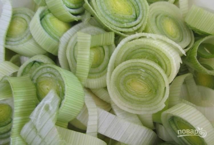1.Отрежьте корневую часть лука-порей, затем нарежьте его кусочками и выложите в миску с водой, оставьте на 15 минут, чтобы вышла грязь.