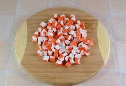 3. Крабовые палочки почистите и нарежьте кубиками.